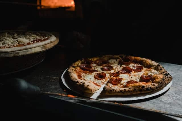 Woodfired Pepperoni Pizza, the oven in the background glowing