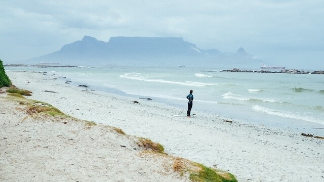 Woman standing in the distance on the ebach at the oceans edge with Table Mountain in the distance behind the woman