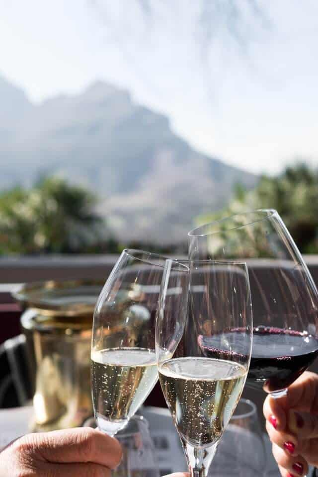 Two champagne flutes and one gladd of red wine being held together in a cheers, in focus, with the Stellenbosch mountains in the background