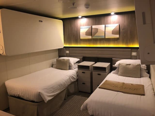 Inside cabin on Britannia Cruise ship with twin beds and bedside tables in between the beds