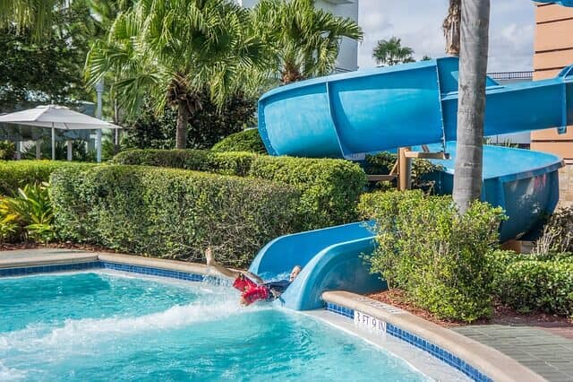 A blue water side tube twisting around into a pool flanked by green hedges either side with a child exiiting the slide feet first into the water