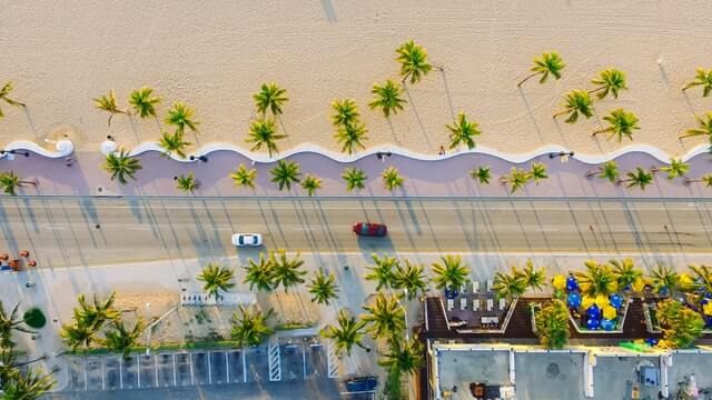 Top down shot of a beach, the road next to it and the buildings opposite the beach