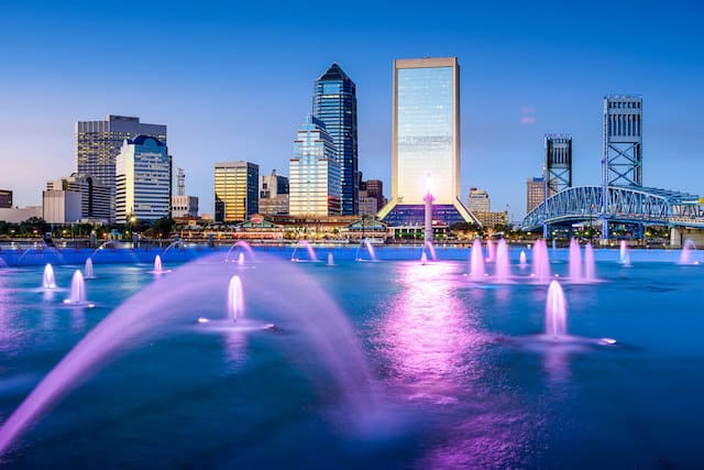 a lake with multiple lit up fountains glowing purple in front of the city sykline at dusk
