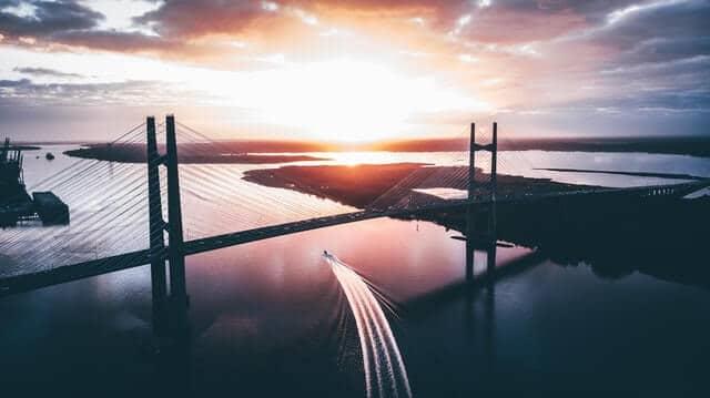 Jacksonville bridge at sunrise, bridge in silohuette with a speedboad sailing underneath leaving a wake trail behind