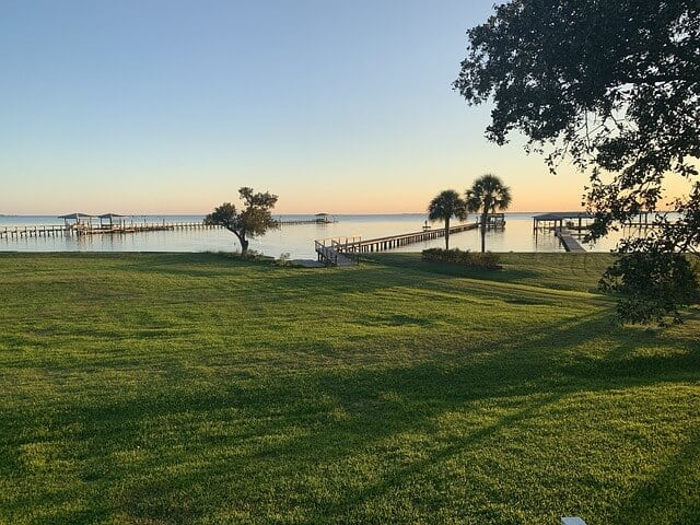 Foreshore at Lake Charles with expansive green grass leafing to a flat lake with a couple trees at the waters edge