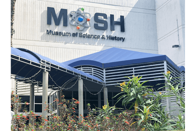 Large MOSH sign on the side of a white building with a blue covered walkway leading to the door under the sign