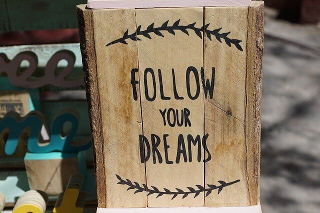 Wooden board with black lettering that says 'Follow Your Dreams'
