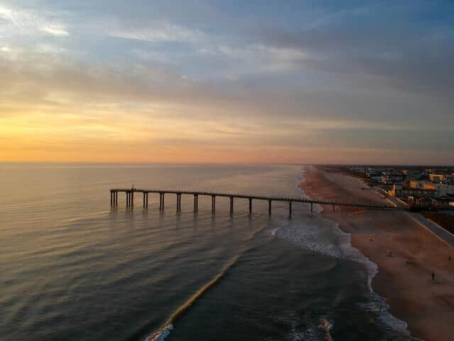 Long wooden pier stretching out into the ocean at sunset