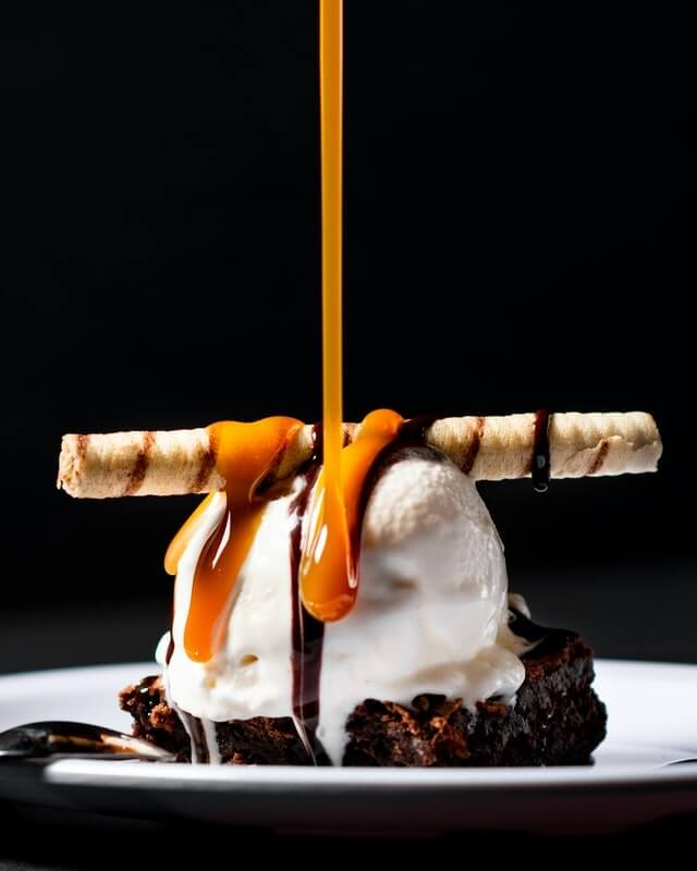 A chocolate brownie on a round white place with a scoop of vanilla ice cream on top, plus a twille and a drip of caramel sauce being poured over the whole thing