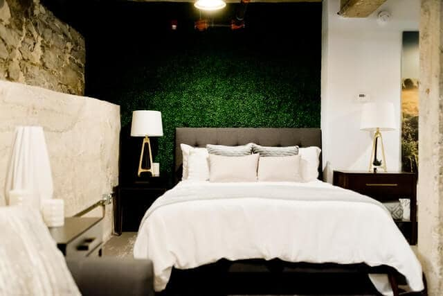 Hotel room with green grass textured wall behind a double bed with white bedding and off white throw cushions. A black bedside table sits on e right with a white lamp sitting on top of it