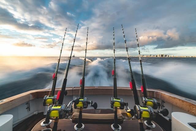 4 Fishing lines at the back of a small boat with the wake behind and a city skyline in the distance
