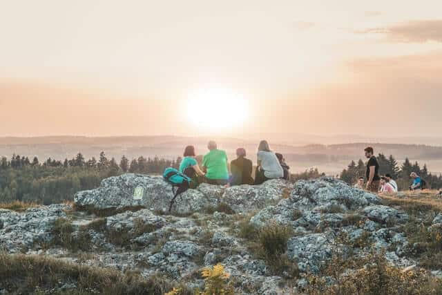 Group of hikers watching the sunset taking a break sitting on top of a rock