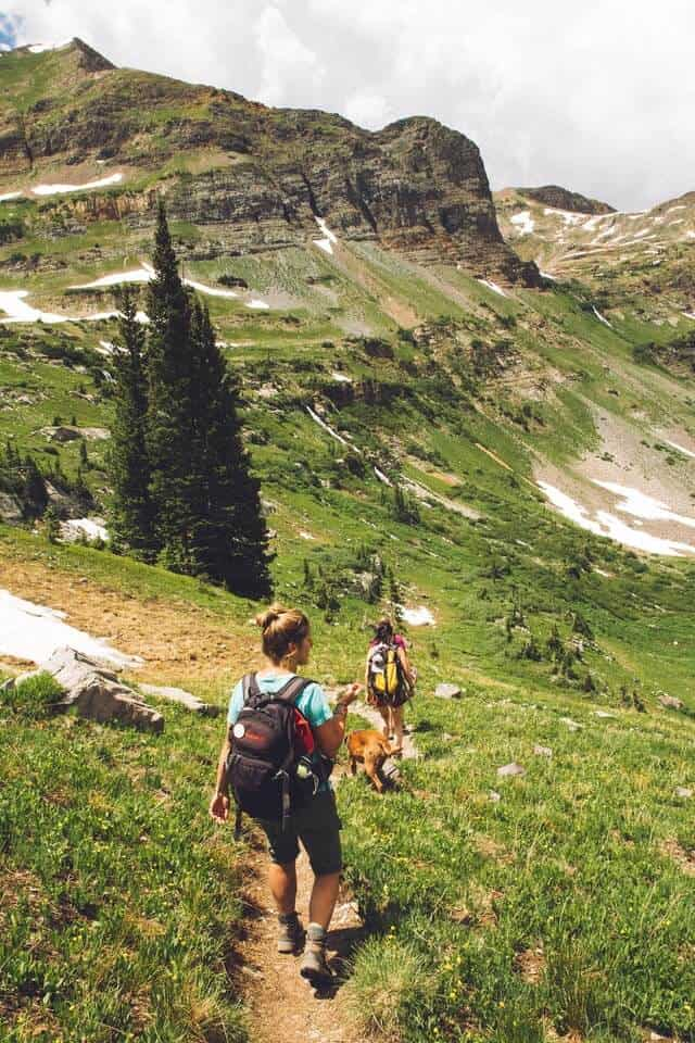 Two female hikers walking down a mountainside grass covered trail