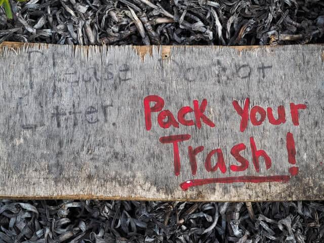 "Wooden sign that says: Please do not litter and in bright red text ""pack your Trash"""