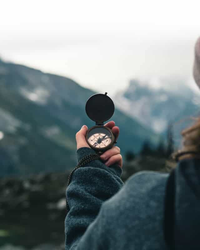 Woman holding an old fashioned compass in front of a misty mountain background