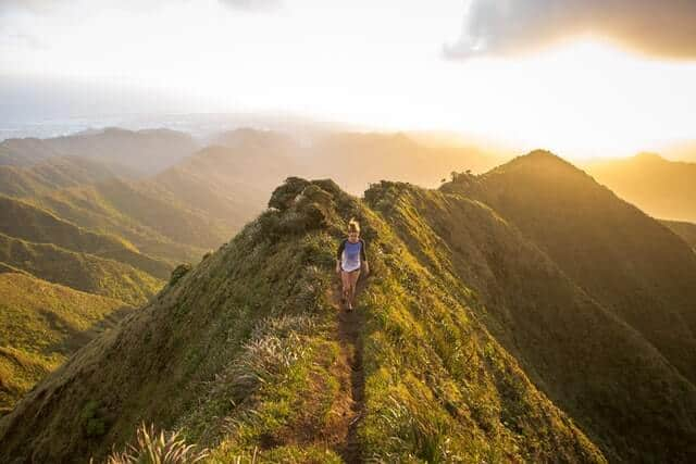 Woman hiking with no hiking essentials on a mountain top path at sunset