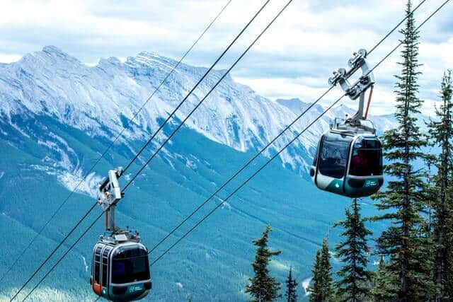 Banff Gondola carriages passing each other with the mountains in the background