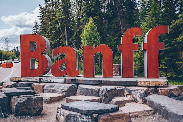 Banff Town Sign - large letters in red on top of a rocky platform with tall fir trees behind it