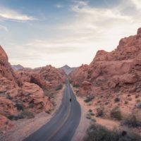 Epic Road Trips from Las Vegas cover photo of a person standing in the middle of the road between a valley of red rocky outcrops