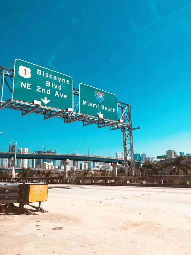 Freeway signs above an empty highway showing directions to Miami Beach