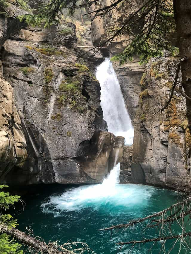 Small waterfall crashing down a rocky cliff into a dark pool of water at Johnstons Canyon