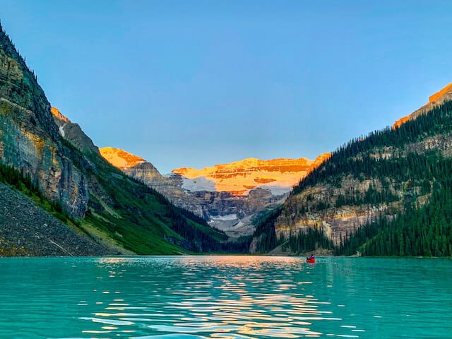 Blue water of Lake Louise at sunrise, a person in a red canoe in the distance towards the mountains of the background