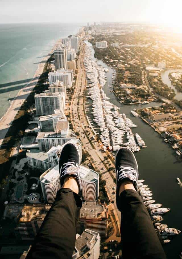 Womans feet wearing back trainers sticking out over the city of Miami below, while flying in a helicopter