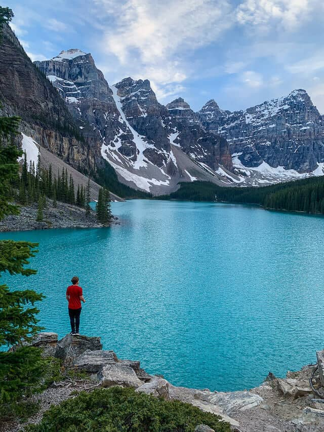 Vibrant blue Moraine Lake, surrounded by the rocky mountains with a person wearing a red jacket standing in the foreground