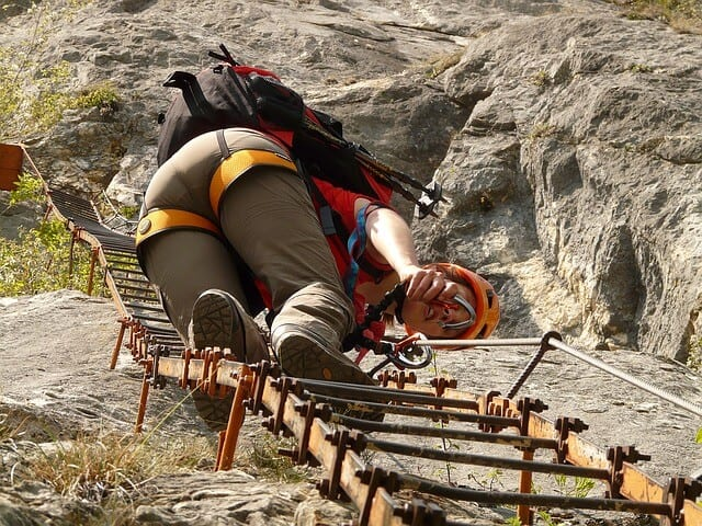 Woman climbing up a steel ladder built into the cliffside wearing hiking pants, a backpack, red tshirt and crash helmet