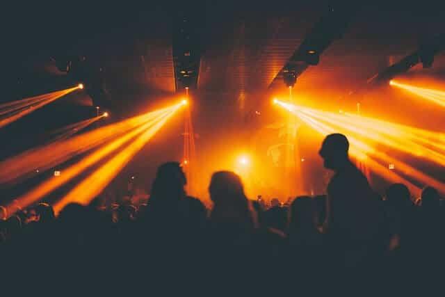 Busy nightlub with yellow-orange strobe lights