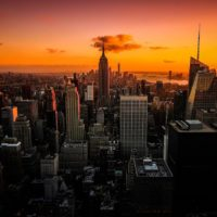 Perfect Itinerary for One Day in New York City (By A Local) header image of the New York skyline from above at sunset backed by shaed of orange and purple