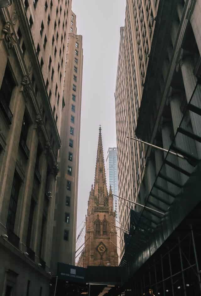 Spire of Trinity Chruch between sky scrapers in New York