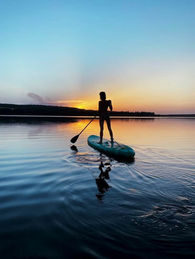 Woman on a Stand Up Paddle Board on flat water at sunrise with a rocky ridge in the background