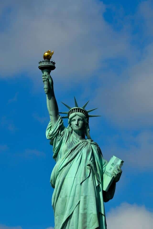 Statue of Liberty New York City with a blue sky behind her green structure