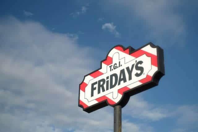 TGI Fridays sign on a tall pole against a blue sky