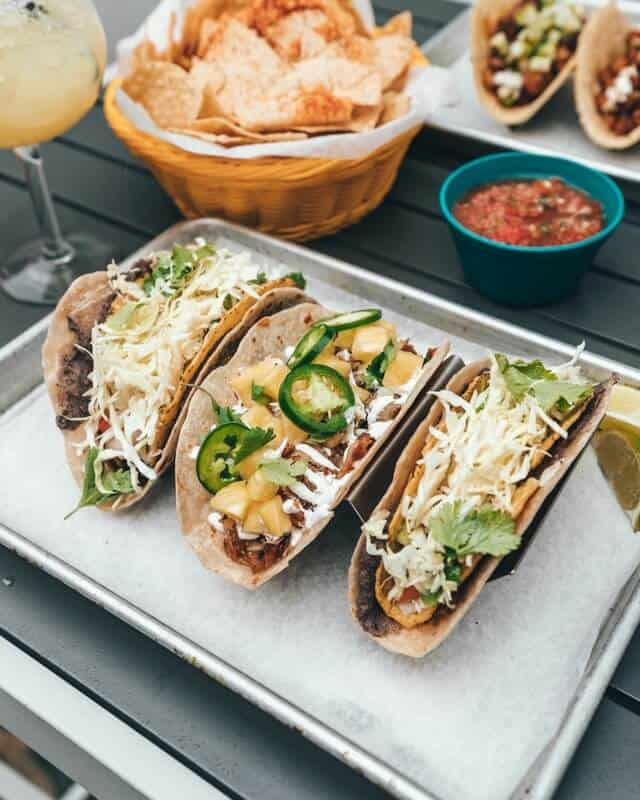 Three tacos on a tray next to two bowls of dips wand an orange cocktail in a tall wine glass