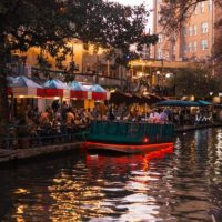Fun Things to do in San Antonio cover photo of the Riverwalk at dusk with people sitting at a bar under umberellas next to a parked boat.