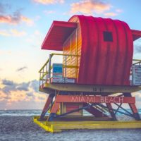 Tips for visiting Miami on a budget cover photo of a colourful lifeguard stand facing the ocean at sunset