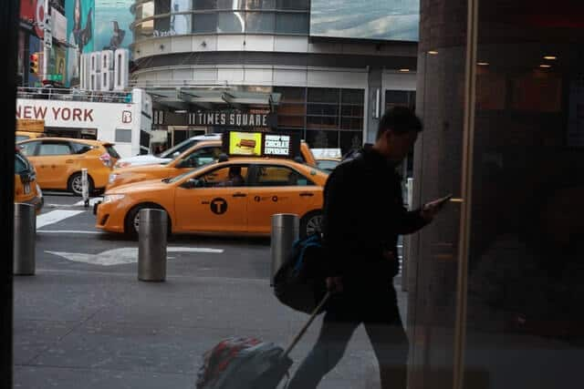 Yellow Cabs on the street in the background with a man pulling a wheeled suitcase into a building while looking at his phone