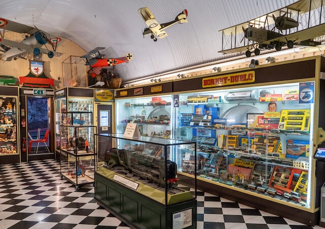 Inside Brighton Toy and Model Museum with checkerboard black and white floor, glass diplay cases of different toy brands and model airplanes hanging from the ceiling