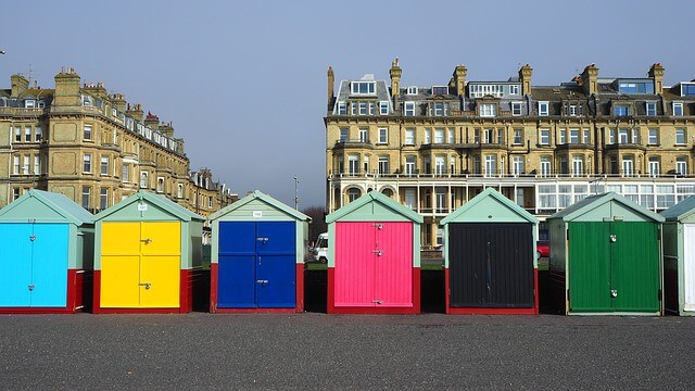 Hove Beach Huts - colurful bathing boxes in front of Victorian era buildings behind them