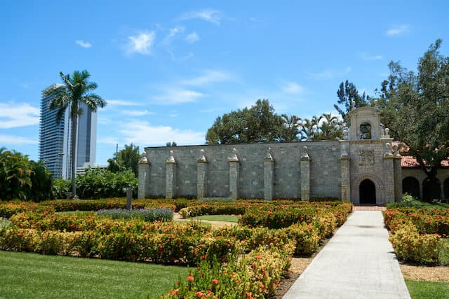 Spanish stone monastary surrounded by manicured gardens under a clear blue sky