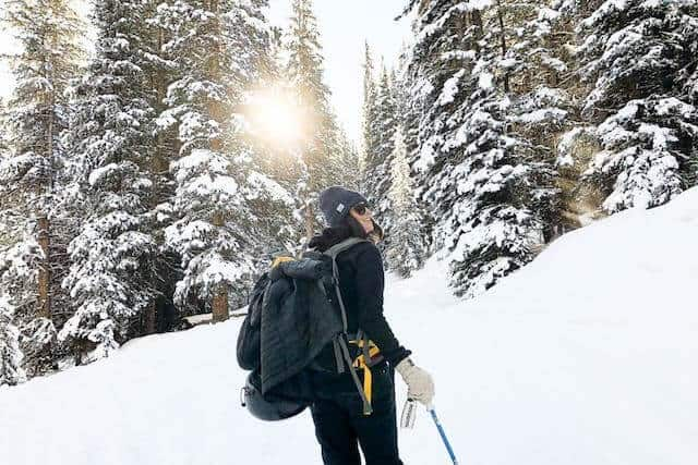 Camping in WInter - woman facing away from the camera hiking with ski poles dressed in snow gear with snow covered fir trees in the background