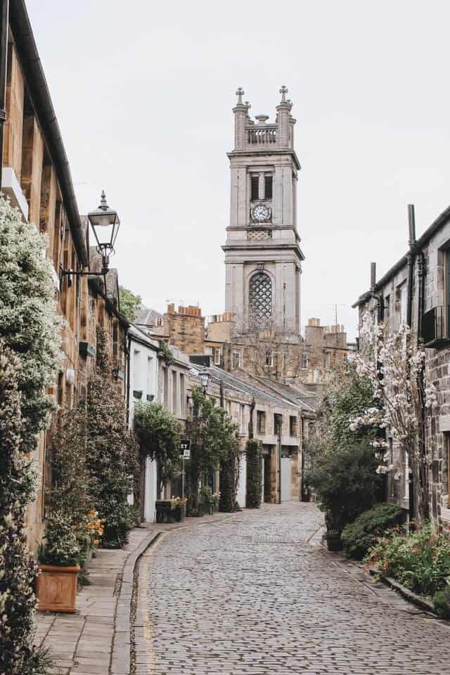 Curved circus lane in Edinburgh with the chirch spire standing tall above the mews houses at the back of the shot