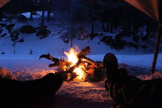Colorado Camping looking out of the open door of the tent, two sets of legs and feet stickout out towards the campfire outside with a snowy bank in the background