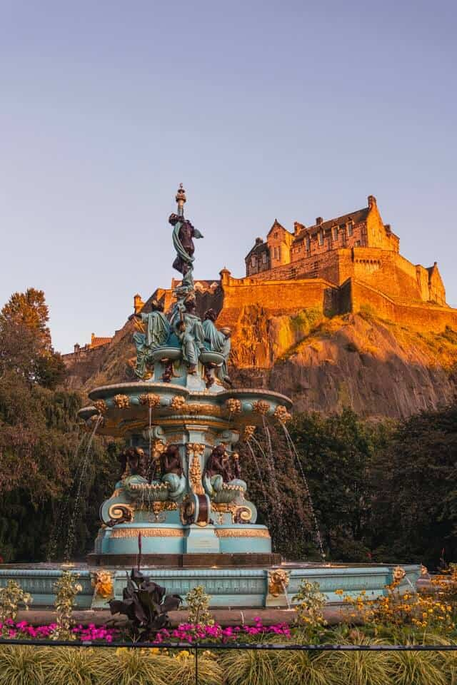 Princes Street Gardens Edinburgh behind the fountain looking up towards the castle on the hill behind it bathed in light at sunset