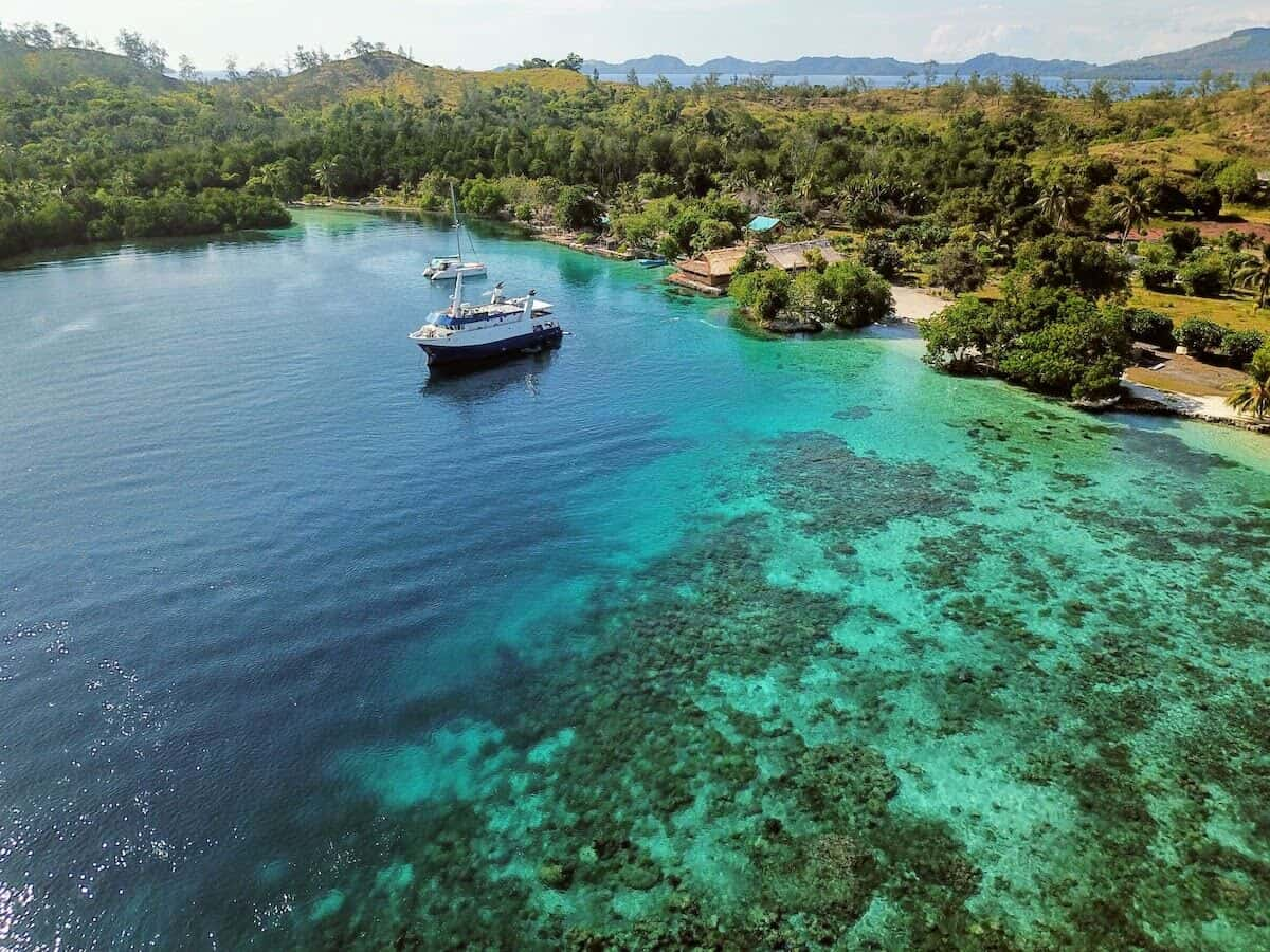Solomon Islands Facts to know before you go - aerial shot of the Russell Islands with a small ship anchored off the shore with lighter patches of coral reef