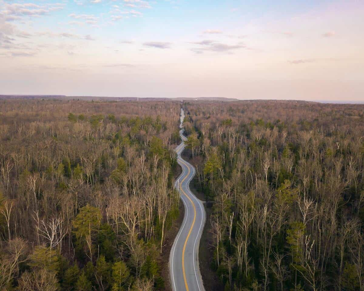 Incredible Wisconsin Road Trips cover image of a paved road winding through a wooden area taken from above