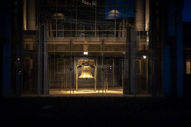 Liberty Bell lit up at night behind a glass wall in Philadelphia