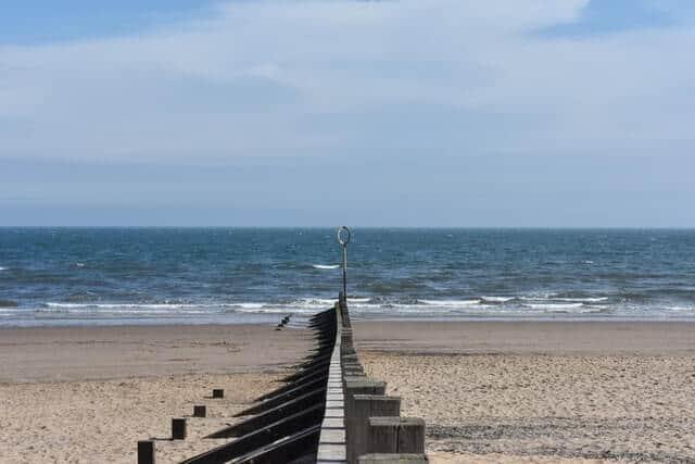 Wooden wave braker line (groyne) leading down to the ocean on Portobello Beach Edinburgh(